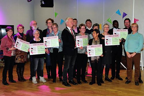 Foto van een groep mensen met cheques in hun handen